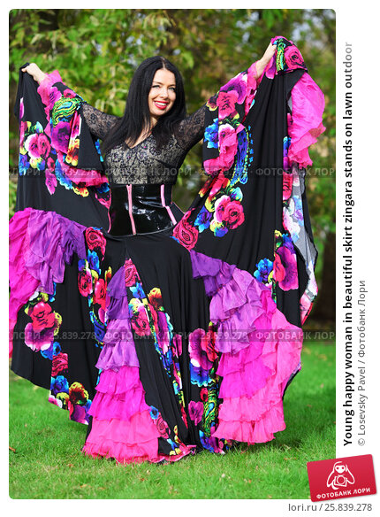 Купить «Young happy woman in beautiful skirt zingara stands on lawn outdoor», фото № 25839278, снято 15 октября 2015 г. (c) Losevsky Pavel / Фотобанк Лори