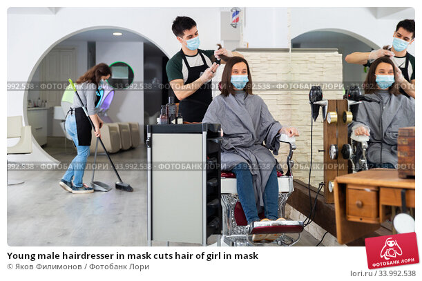 Young male hairdresser in mask cuts hair of girl in mask. Стоковое фото, фотограф Яков Филимонов / Фотобанк Лори