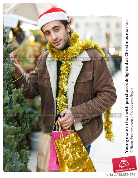 Young male in hat with purchases delighted at Christmas market. Стоковое фото, фотограф Яков Филимонов / Фотобанк Лори