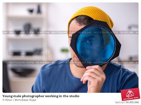 Young male photographer working in the studio. Стоковое фото, фотограф Elnur / Фотобанк Лори