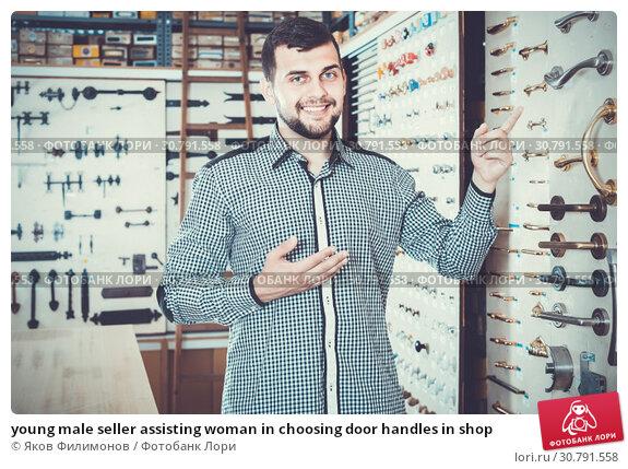 Купить «young male seller assisting woman in choosing door handles in shop», фото № 30791558, снято 5 апреля 2017 г. (c) Яков Филимонов / Фотобанк Лори