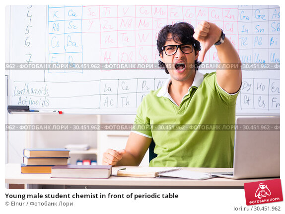Young male student chemist in front of periodic table. Стоковое фото, фотограф Elnur / Фотобанк Лори