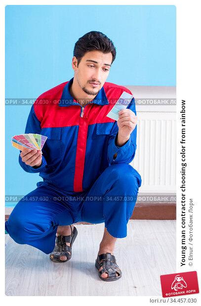 Young man contractor choosing color from rainbow. Стоковое фото, фотограф Elnur / Фотобанк Лори