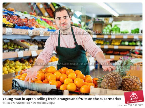 Young man in apron selling fresh oranges and fruits on the supermarket. Стоковое фото, фотограф Яков Филимонов / Фотобанк Лори