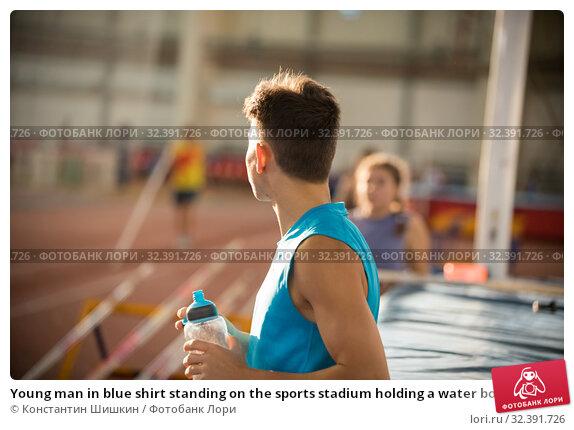 Купить «Young man in blue shirt standing on the sports stadium holding a water bottle», фото № 32391726, снято 1 ноября 2019 г. (c) Константин Шишкин / Фотобанк Лори