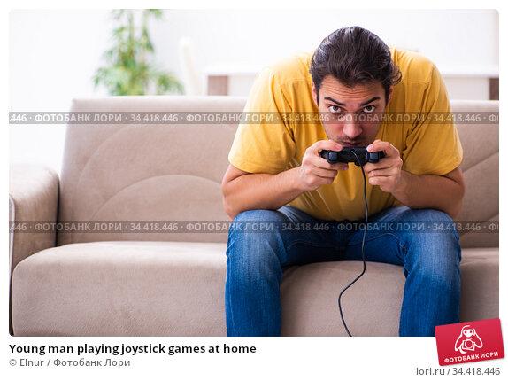 Young man playing joystick games at home. Стоковое фото, фотограф Elnur / Фотобанк Лори