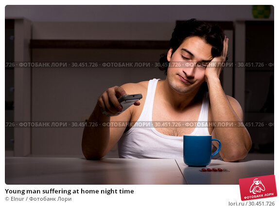 Young man suffering at home night time. Стоковое фото, фотограф Elnur / Фотобанк Лори