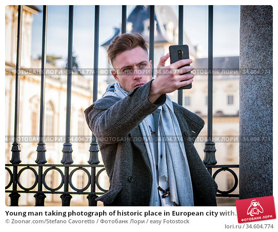 Young man taking photograph of historic place in European city with... Стоковое фото, фотограф Zoonar.com/Stefano Cavoretto / easy Fotostock / Фотобанк Лори