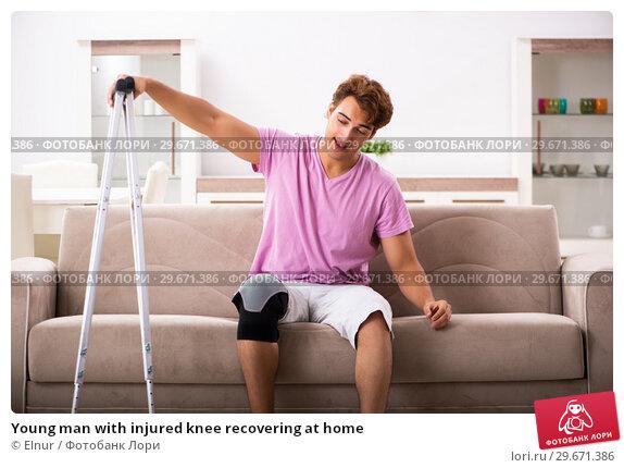 Купить «Young man with injured knee recovering at home», фото № 29671386, снято 4 сентября 2018 г. (c) Elnur / Фотобанк Лори