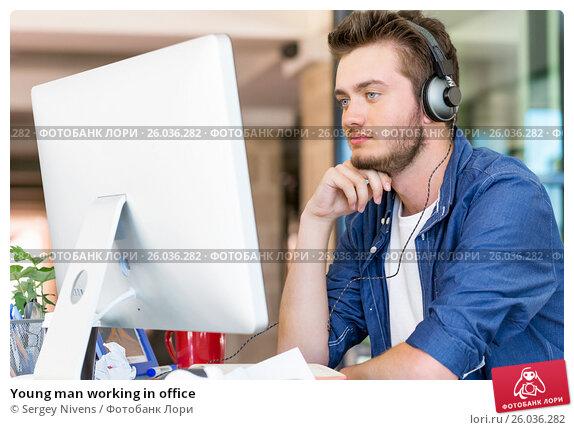 Young man working in office, фото № 26036282, снято 13 декабря 2014 г. (c) Sergey Nivens / Фотобанк Лори