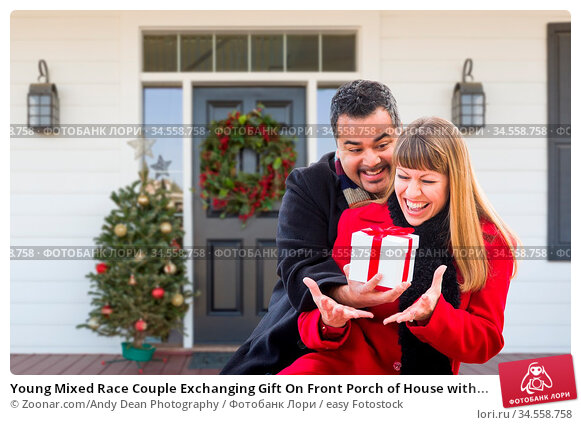 Young Mixed Race Couple Exchanging Gift On Front Porch of House with... Стоковое фото, фотограф Zoonar.com/Andy Dean Photography / easy Fotostock / Фотобанк Лори