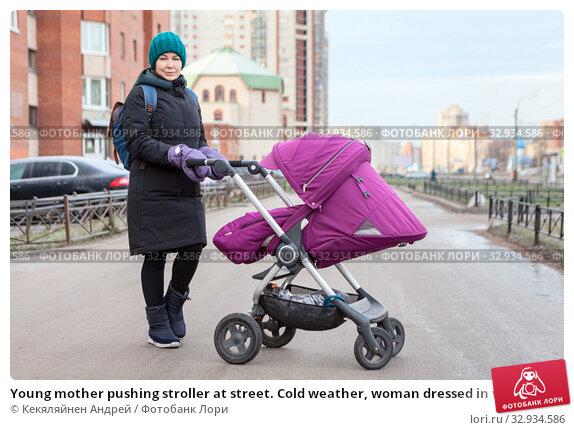 Купить «Young mother pushing stroller at street. Cold weather, woman dressed in warm clothing with windbreaker mittens», фото № 32934586, снято 11 декабря 2019 г. (c) Кекяляйнен Андрей / Фотобанк Лори