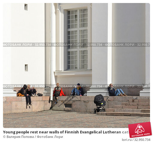 Young people rest near walls of Finnish Evangelical Lutheran cathedral of Diocese. Helsinki, Suomi (2018 год). Редакционное фото, фотограф Валерия Попова / Фотобанк Лори