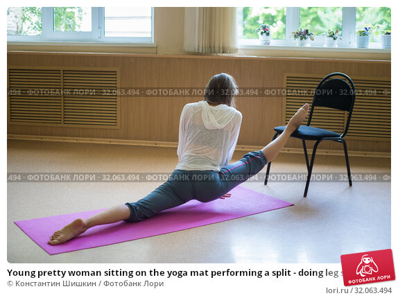 Young pretty woman sitting on the yoga mat performing a split - doing leg stretching exercises using a chair. Стоковое фото, фотограф Константин Шишкин / Фотобанк Лори