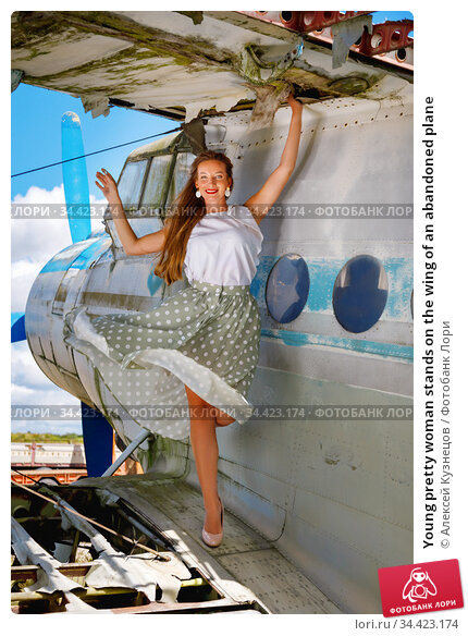 Young pretty woman stands on the wing of an abandoned plane. Стоковое фото, фотограф Алексей Кузнецов / Фотобанк Лори