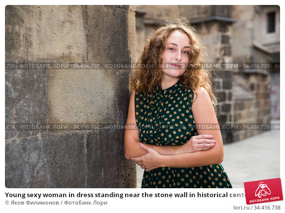 Young sexy woman in dress standing near the stone wall in historical center. Стоковое фото, фотограф Яков Филимонов / Фотобанк Лори
