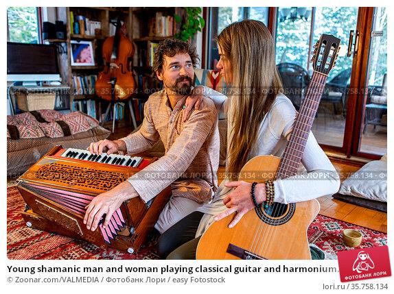 Young shamanic man and woman playing classical guitar and harmonium... Стоковое фото, фотограф Zoonar.com/VALMEDIA / easy Fotostock / Фотобанк Лори