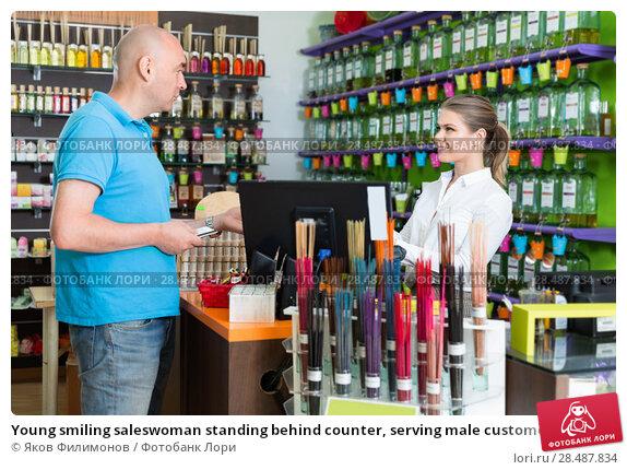 Купить «Young smiling saleswoman standing behind counter, serving male customer in perfume shop», фото № 28487834, снято 24 апреля 2018 г. (c) Яков Филимонов / Фотобанк Лори