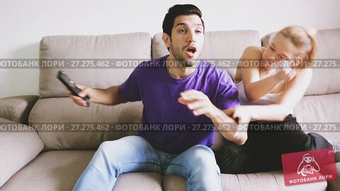 Young upset woman trying to take away TV remote from her boyfriend. Стоковое видео, видеограф Яков Филимонов / Фотобанк Лори