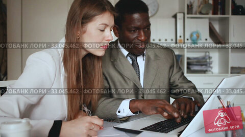 Young woman and man colleagues working with laptop and papers in office. Стоковое видео, видеограф Яков Филимонов / Фотобанк Лори