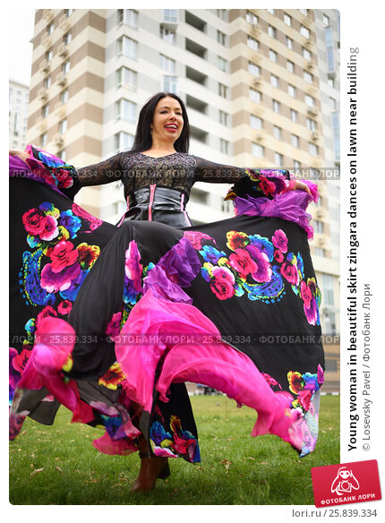 Купить «Young woman in beautiful skirt zingara dances on lawn near building», фото № 25839334, снято 15 октября 2015 г. (c) Losevsky Pavel / Фотобанк Лори