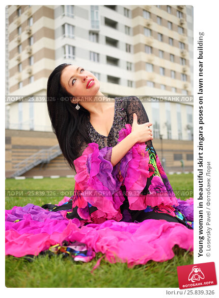 Купить «Young woman in beautiful skirt zingara poses on lawn near building», фото № 25839326, снято 15 октября 2015 г. (c) Losevsky Pavel / Фотобанк Лори