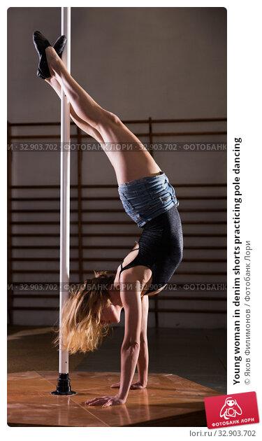 Купить «Young woman in denim shorts practicing pole dancing», фото № 32903702, снято 16 февраля 2020 г. (c) Яков Филимонов / Фотобанк Лори