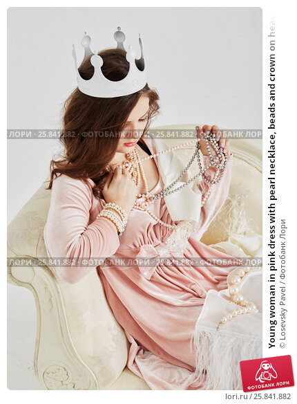 Купить «Young woman in pink dress with pearl necklace, beads and crown on head sits on couch», фото № 25841882, снято 7 марта 2015 г. (c) Losevsky Pavel / Фотобанк Лори