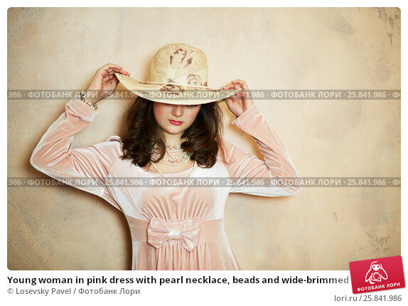 Купить «Young woman in pink dress with pearl necklace, beads and wide-brimmed hat on head at wall in studio», фото № 25841986, снято 7 марта 2015 г. (c) Losevsky Pavel / Фотобанк Лори