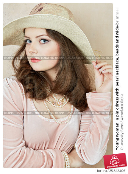 Купить «Young woman in pink dress with pearl necklace, beads and wide-brimmed hat on head at wall in studio», фото № 25842006, снято 7 марта 2015 г. (c) Losevsky Pavel / Фотобанк Лори