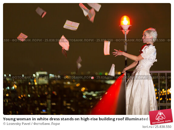Купить «Young woman in white dress stands on high-rise building roof illuminated by red obstruction light and looks at flying thrown out letters», фото № 25838550, снято 13 февраля 2015 г. (c) Losevsky Pavel / Фотобанк Лори