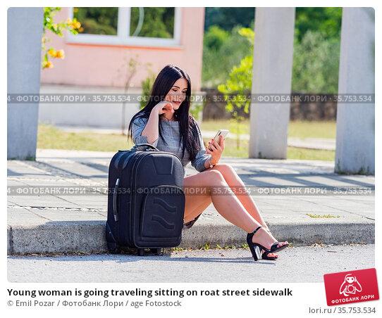 Young woman is going traveling sitting on roat street sidewalk. Стоковое фото, фотограф Emil Pozar / age Fotostock / Фотобанк Лори