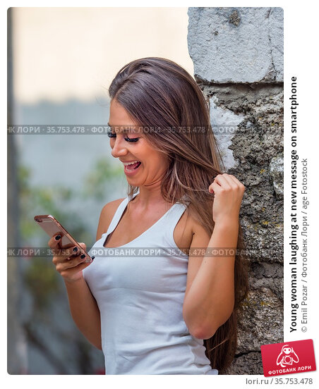 Young woman laughing at new message on smartphone. Стоковое фото, фотограф Emil Pozar / age Fotostock / Фотобанк Лори