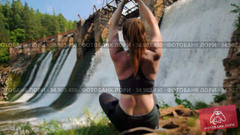 Young woman on vacation doing yoga near the water dam in the forest - meditating. Стоковое видео, видеограф Константин Шишкин / Фотобанк Лори