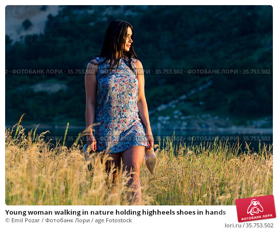 Young woman walking in nature holding highheels shoes in hands. Стоковое фото, фотограф Emil Pozar / age Fotostock / Фотобанк Лори