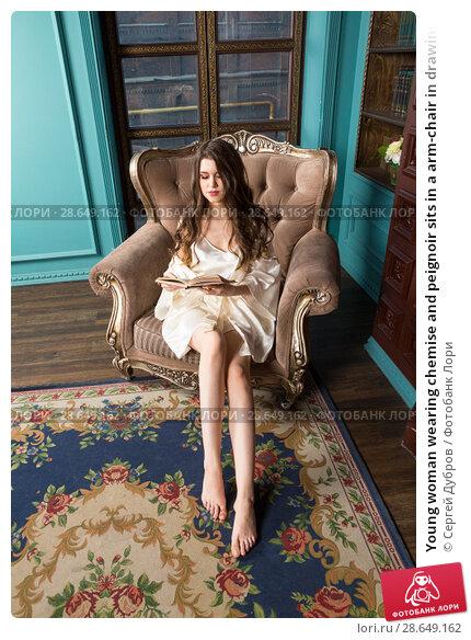 Купить «Young woman wearing chemise and peignoir sits in a arm-chair in drawing room and reads a book», фото № 28649162, снято 1 апреля 2018 г. (c) Сергей Дубров / Фотобанк Лори
