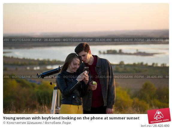 Купить «Young woman with boyfriend looking on the phone at summer sunset», фото № 28420490, снято 14 мая 2018 г. (c) Константин Шишкин / Фотобанк Лори