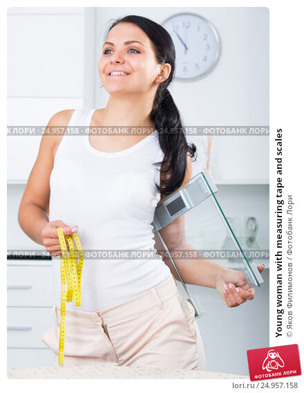 Купить «Young woman with measuring tape and scales», фото № 24957158, снято 23 февраля 2019 г. (c) Яков Филимонов / Фотобанк Лори