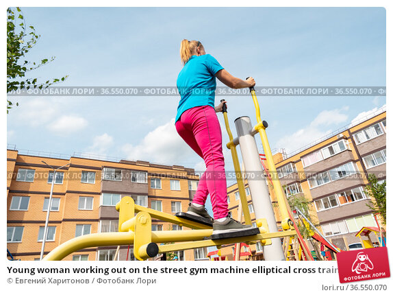 Young woman working out on the street gym machine elliptical cross trainer in a city courtyard. Стоковое фото, фотограф Евгений Харитонов / Фотобанк Лори