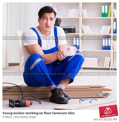 Купить «Young worker working on floor laminate tiles», фото № 32223794, снято 9 марта 2017 г. (c) Elnur / Фотобанк Лори