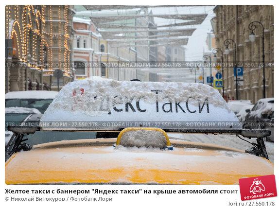 """Купить «Желтое такси с баннером """"Яндекс такси"""" на крыше автомобиля стоит на улице и ждет клиента у ГУМа во время снегопада в городе Москве, Россия», фото № 27550178, снято 4 февраля 2018 г. (c) Николай Винокуров / Фотобанк Лори"""