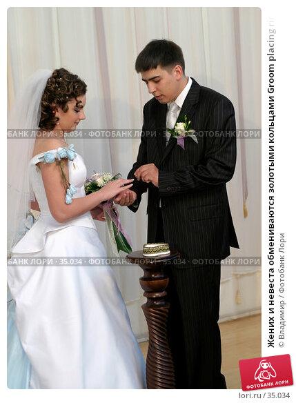 Купить «Жених и невеста обмениваются золотыми кольцами Groom placing ring on brides hand», фото № 35034, снято 16 сентября 2005 г. (c) Владимир / Фотобанк Лори