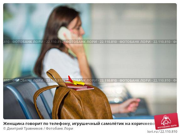 Купить «Женщина говорит по телефону, игрушечный самолётик на коричневой сумке», фото № 22110810, снято 10 июня 2015 г. (c) Дмитрий Травников / Фотобанк Лори