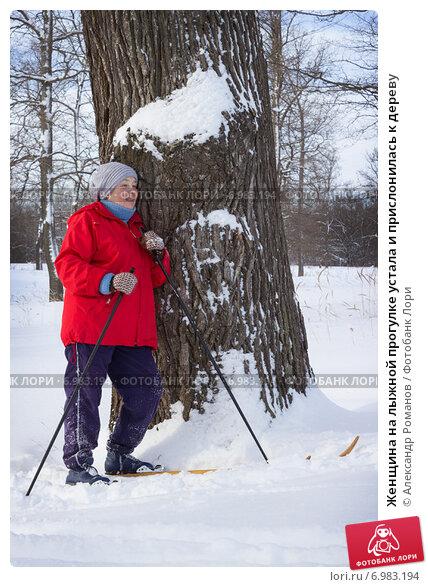 Женщина на лыжной прогулке устала и прислонилась к дереву. Стоковое фото, фотограф Александр Романов / Фотобанк Лори