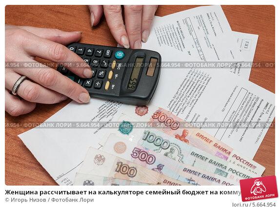 Купить «Женщина рассчитывает на калькуляторе семейный бюджет на коммунальные расходы», эксклюзивное фото № 5664954, снято 3 марта 2014 г. (c) Игорь Низов / Фотобанк Лори