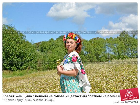 Зрелая  женщина с венком на голове и цветастым платком на плече на фоне цветущего гречишного поля, фото № 26766794, снято 29 июля 2017 г. (c) Ирина Борсученко / Фотобанк Лори
